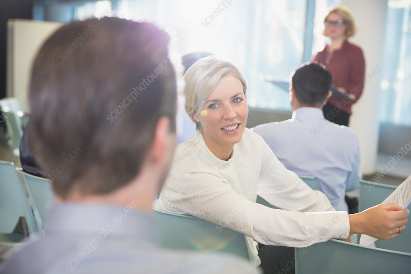 Smiling businesswoman talking to businessman