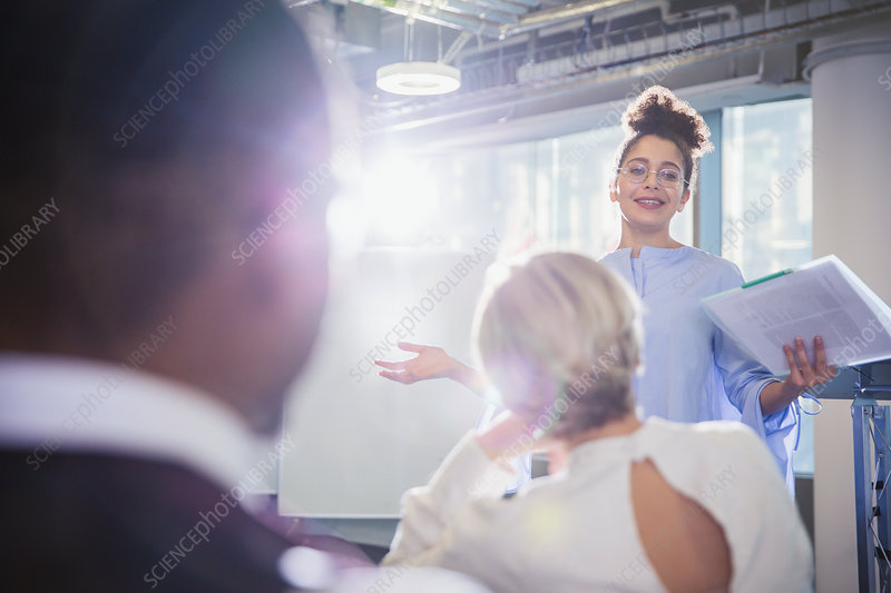 Businesswoman with paperwork leading meeting
