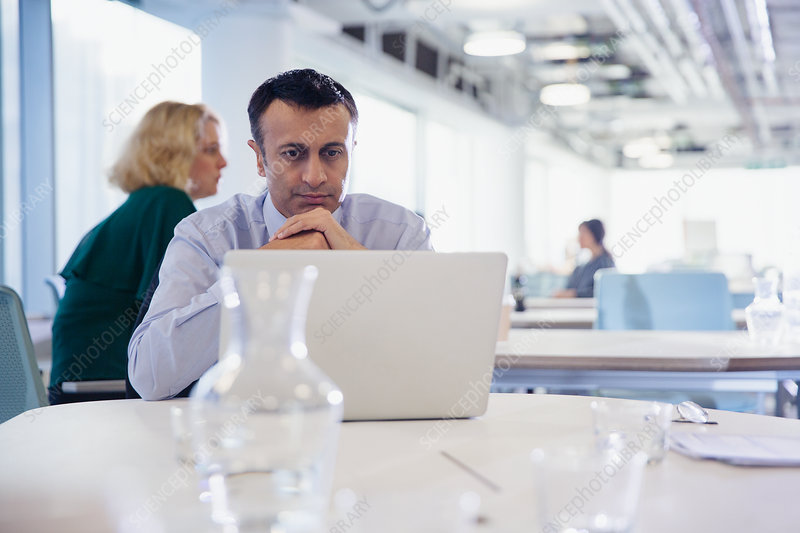 Focused, serious businessman working at laptop