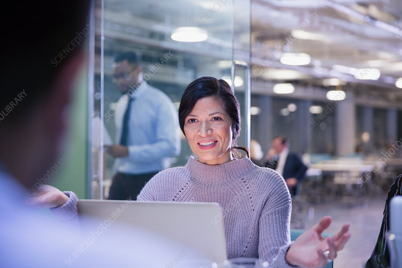Businesswoman gesturing, talking at laptop