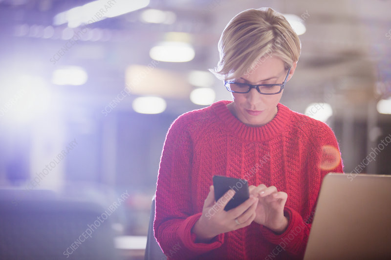 Businesswoman working late at laptop, texting