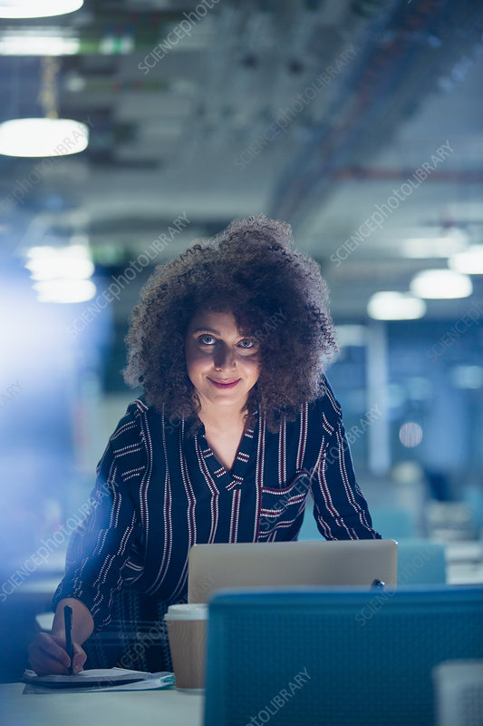 Portrait businesswoman working late at laptop