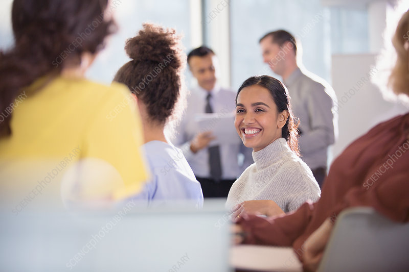 Smiling businesswoman talking to colleagues