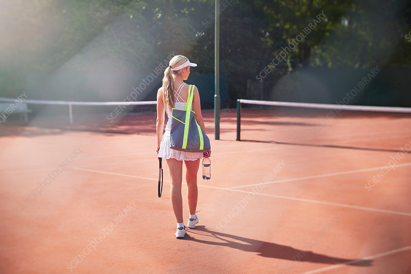 Young female tennis player walking