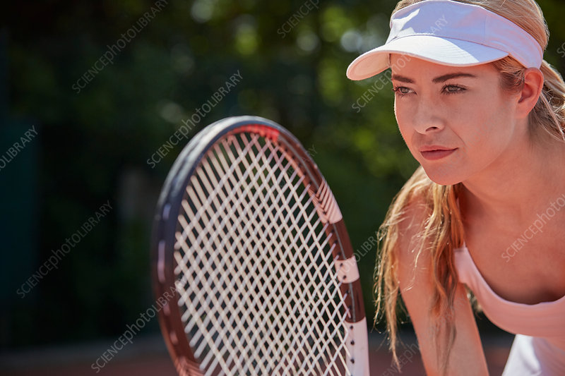 Focused tennis player holding tennis racket