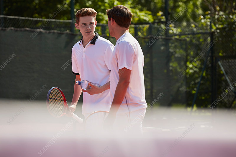 Male tennis players with tennis rackets talking