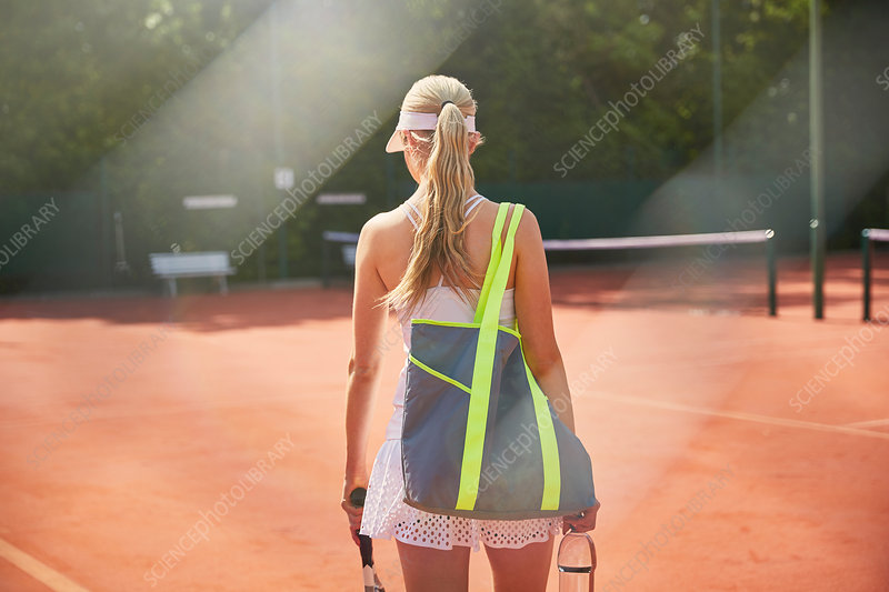 Young tennis player walking with bag
