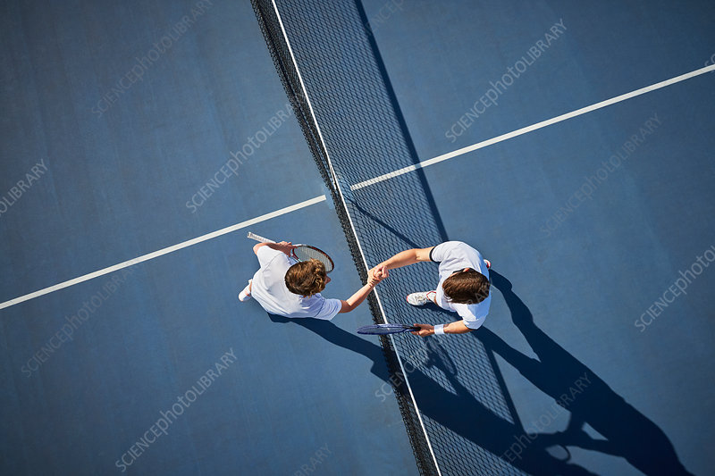 Overhead view tennis players handshaking at net