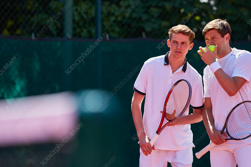 Young tennis doubles players talking, strategizing