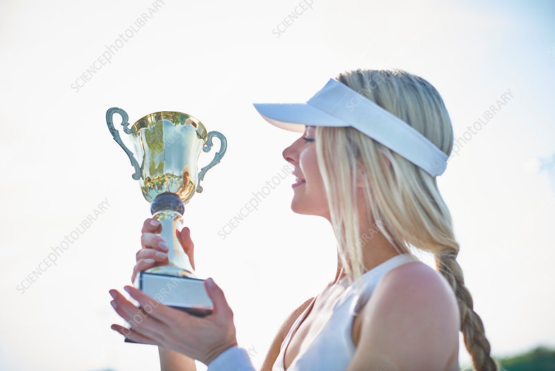 Blonde tennis player holding trophy