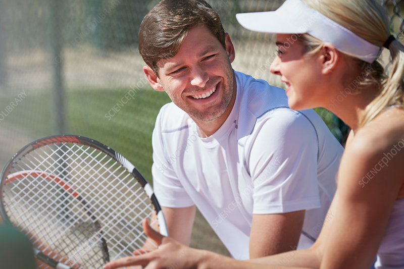 Smiling tennis players resting and talking