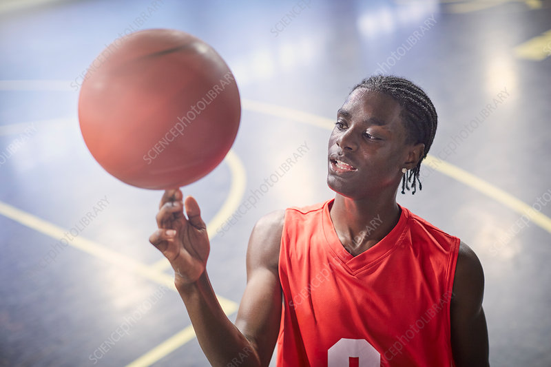 Young basketball player spinning basketball