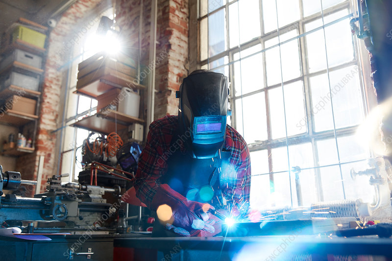Welder welding with welding mask and torch
