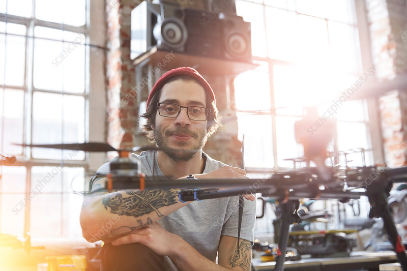 Portrait designer with tattoos working on drone