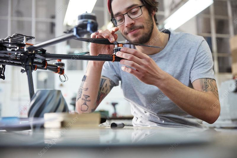 Male designer with tattoos assembling drone