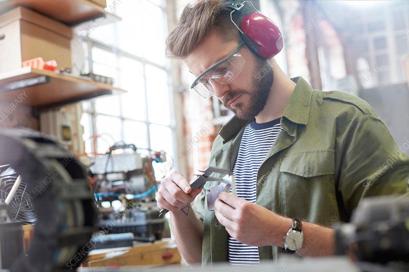 Male designer using caliper in workshop