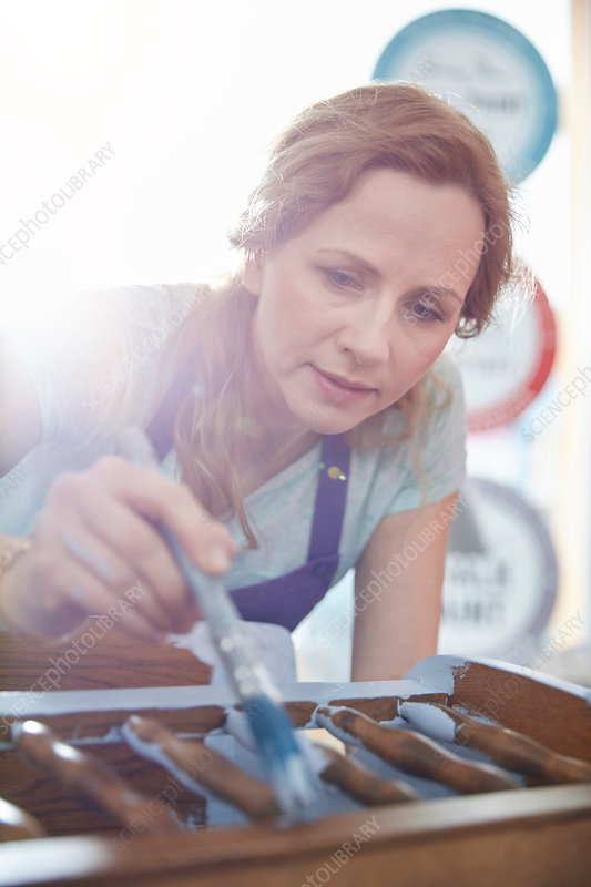 Focused painter painting furniture with blue paint