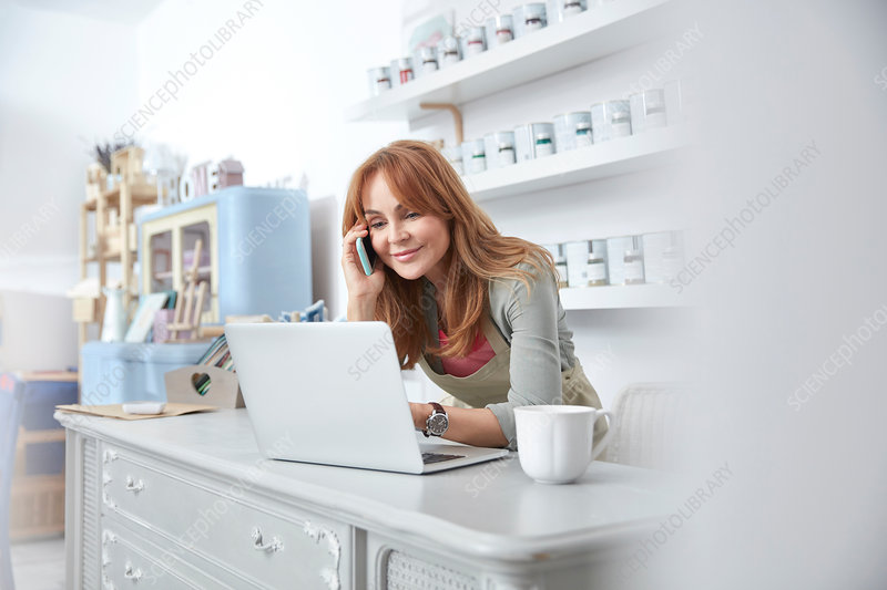 Smiling business owner using laptop at counter