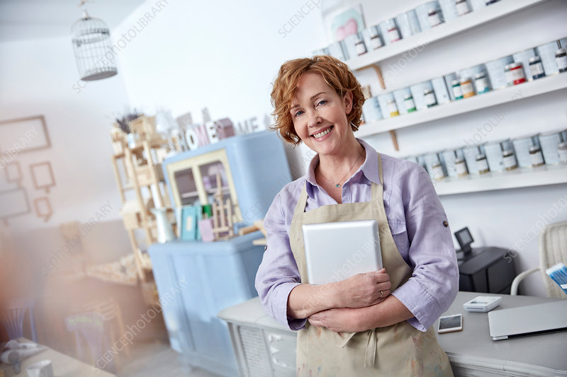 Portrait business owner holding tablet in art shop
