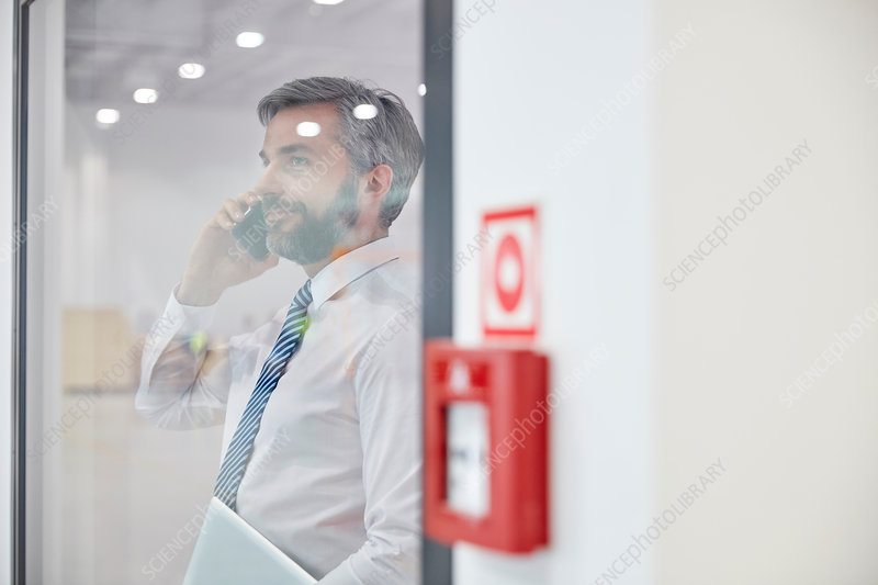 Male supervisor talking on cell phone at window