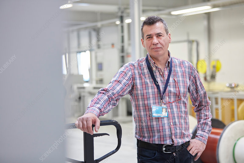 Portrait confident worker in fiber optics factory