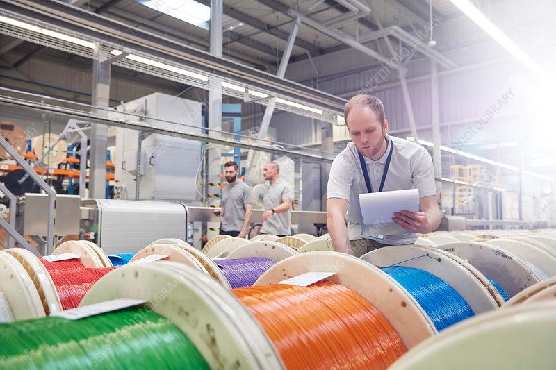 Male worker checking multicolor spools