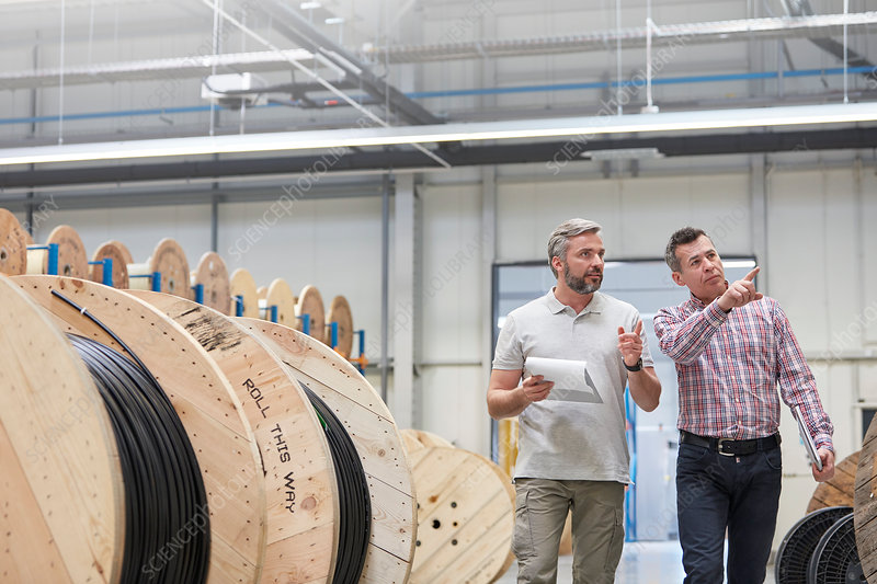 Male supervisor and worker walking along spools