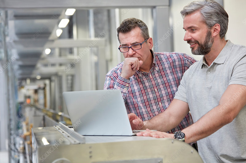 Male supervisors using laptop in factory