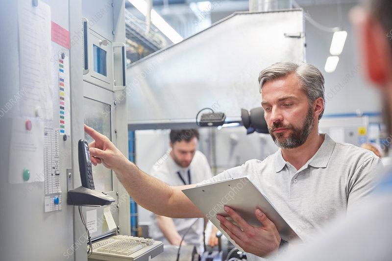 Male supervisor using machinery control panel