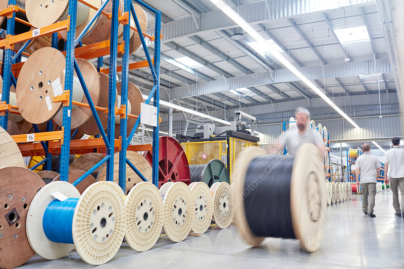 Male worker rolling large spool
