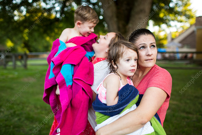 Lesbian mothers holding children wrapped in towel