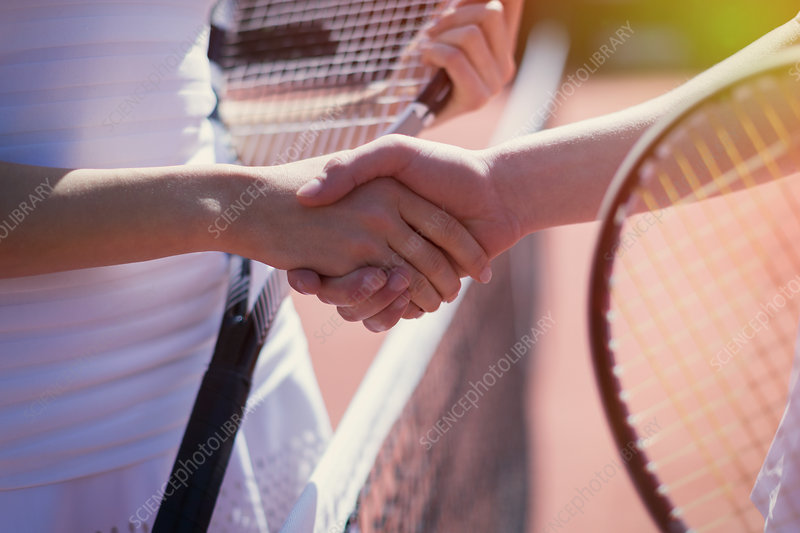 Close up tennis players handshaking at net