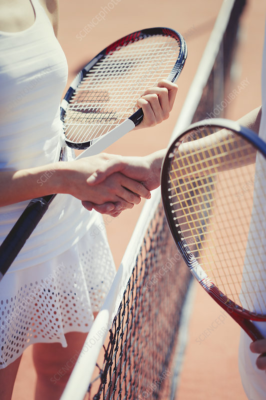 Tennis players handshaking in sportsmanship at net