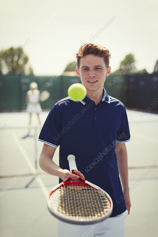 Tennis player bouncing tennis ball on racket