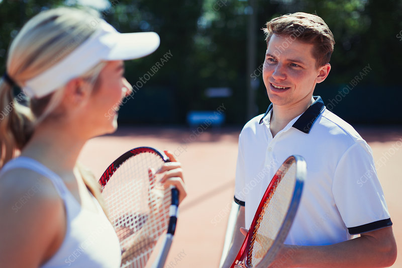 Male and tennis players talking