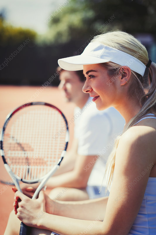 Smiling tennis player holding racket