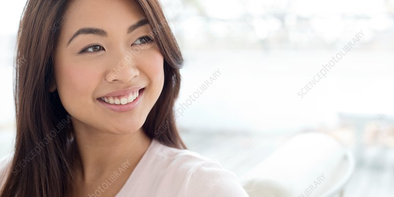 Woman with brown hair smiling and looking away