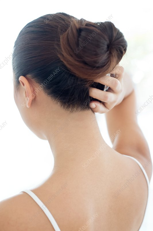 Woman with hair bun scratching head