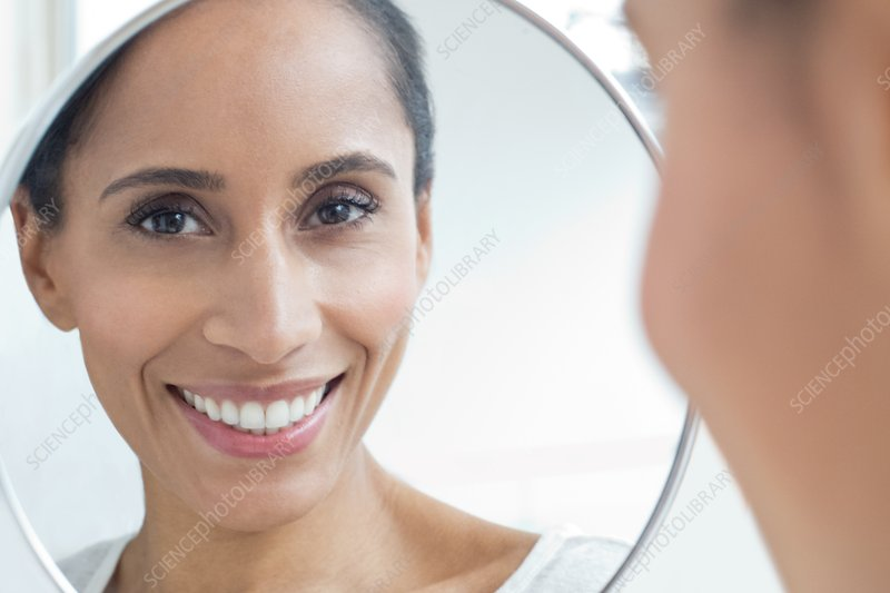 Woman looking in mirror, smiling