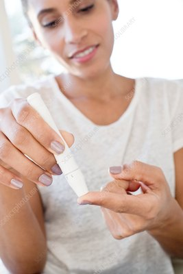 Woman doing pin prick test on finger