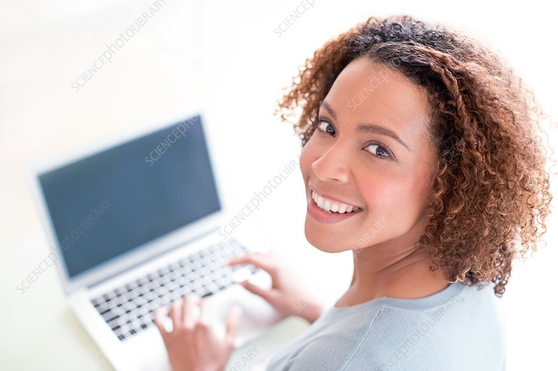 Mid adult woman using laptop