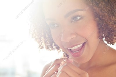 Portrait of woman flossing teeth