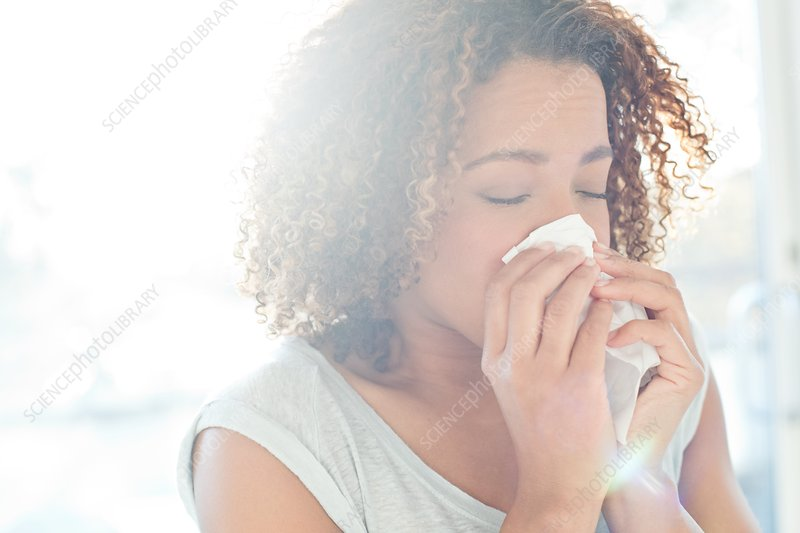 Woman blowing nose on tissue