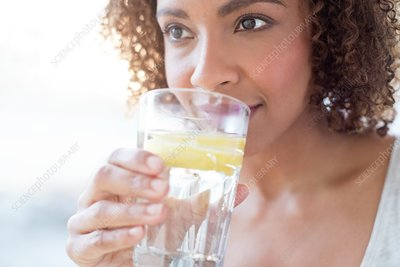 Mid adult woman drinking water