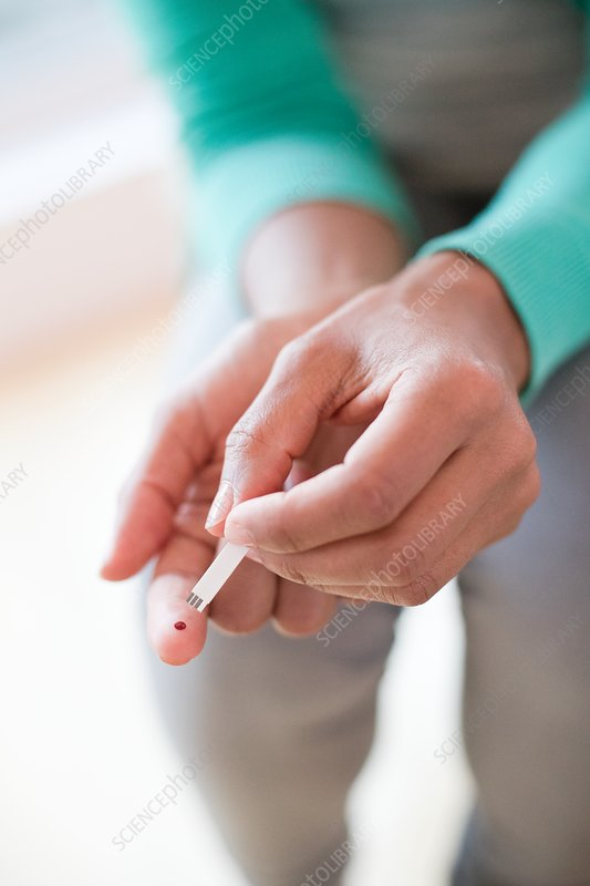 Woman doing finger prick test