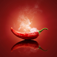 Red chilli with smoke against red background