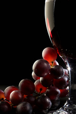 Red grapes and wine in glass, still life