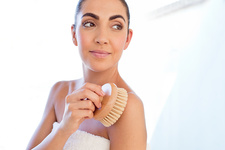 Woman using body brush on shoulder