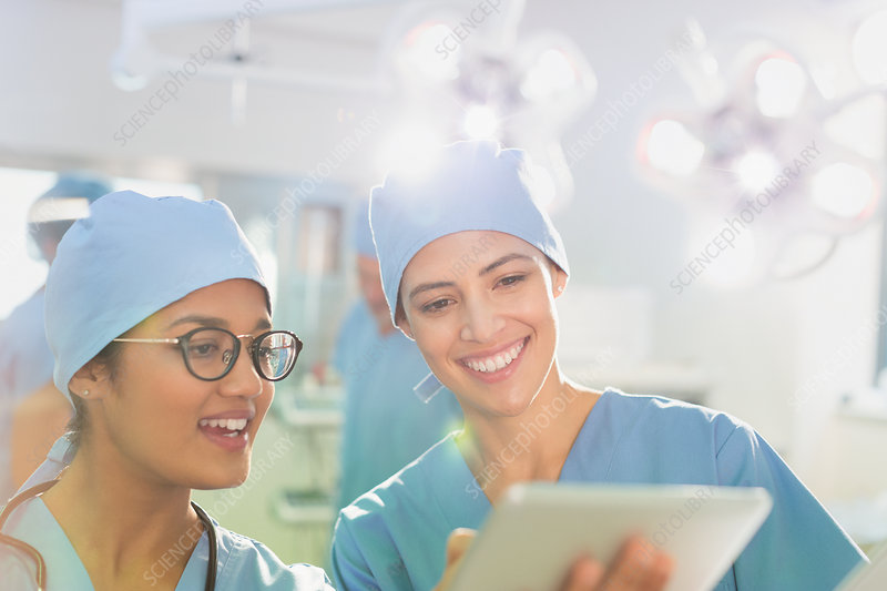 Female surgeons using digital tablet, talking