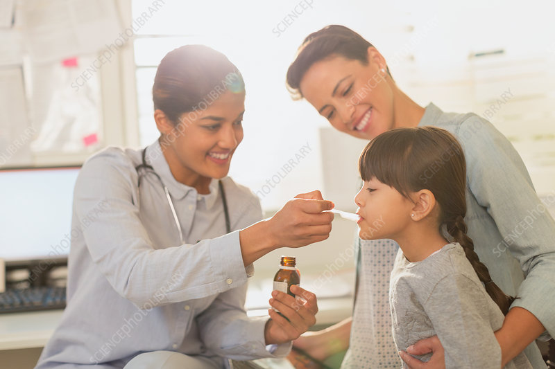 Paediatrician feeding cough syrup to girl patient